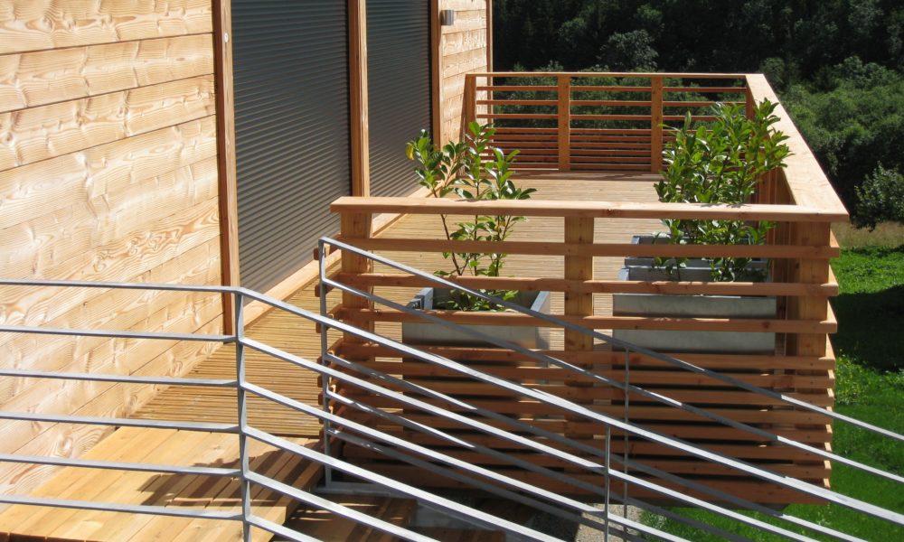 drewniana balustrada tarasu współgra z drewnianą elewacją domu